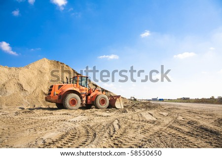 Orange excavator on a construction site working on a pile of gravel. General construction scene