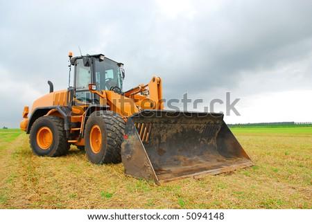 orange excavator on a farmland background - stock photo