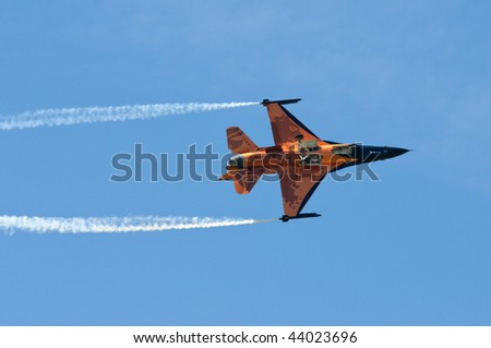 orange F-16 fighting falcon with two smoke trails against blue sky - stock photo
