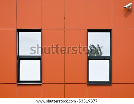 Orange facade of aluminum panels. Two windows and surveillance cameras, which looks onto the street. Close-up. Fragment. - stock photo