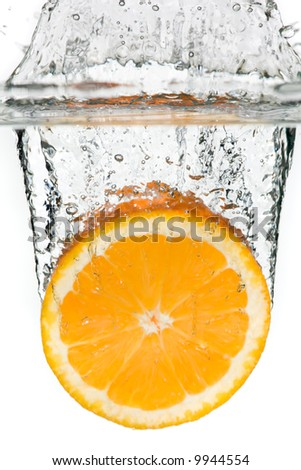Orange falling into the water over white - stock photo