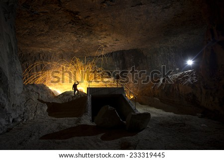 orange firework with silhouette in a cave - stock photo