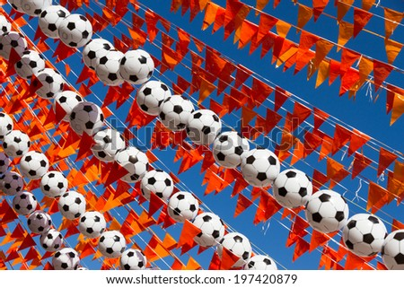 Orange flags (Dutch national color), footballs and a blue sky during the world soccer cup of 2014.  - stock photo