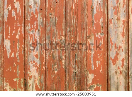 Orange flaky paint on a wooden fence. - stock photo