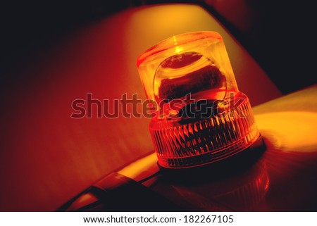 Orange flashing and revolving light on top of a support and services vehicle - stock photo