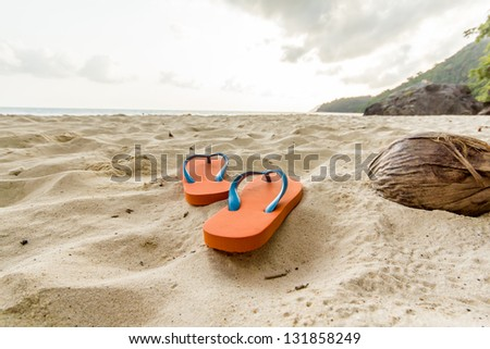 Orange flip-flop on the beach - stock photo