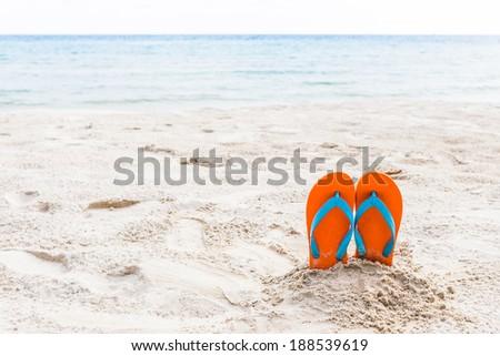 Orange flip-flop on the beach - stock photo