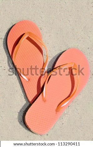 Orange Flip Flops in Sand - stock photo