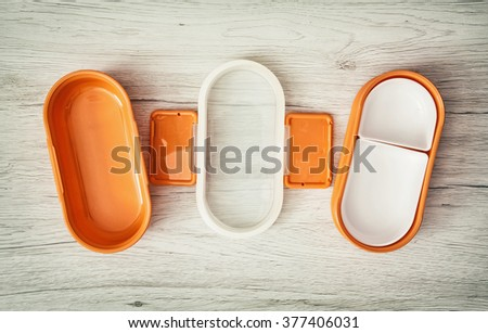 Orange folding plastic box for food storage on the wooden background. - stock photo
