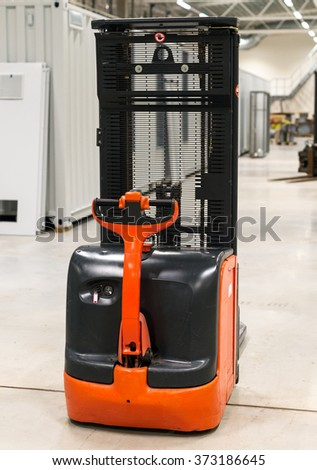 Orange forklift loader in the modern warehouse. - stock photo