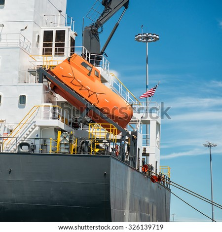 orange free-fall life boat for emergency crew evacuation installed on cargo ship - stock photo