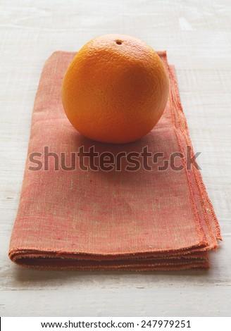 Orange fruit on a burnt orange colored napkin placemat vertical - stock photo
