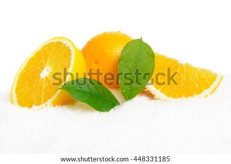 Orange fruits with ice cubes and orange fruit with citrus leaves on ice on white background - stock photo