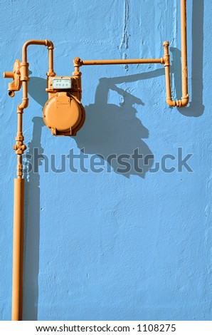 Orange gas meter against blue wall - stock photo