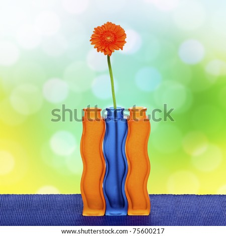 Orange gerbera flower in vase on spring background - stock photo