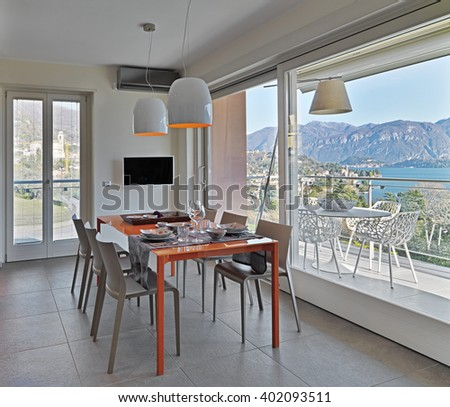 orange glass dining table in the modern kitchen overlooking on the terrace and on the lake - stock photo