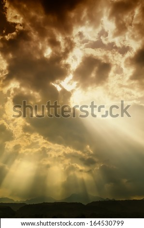 Orange God light shining on mountains - stock photo