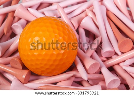Orange golf ball lying between pink wooden golf tees - stock photo