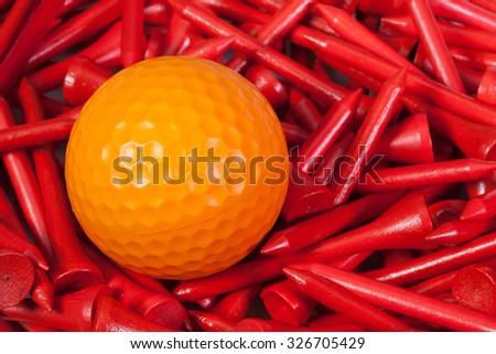 Orange  golf ball lying between red wooden golf tees - stock photo