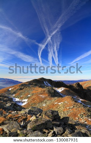 Orange grass, snow patches and distant mountains under the sky marked with airplane traces - stock photo