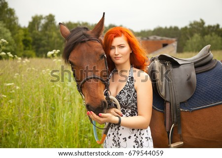 orange hair woman and her brown horse in the field just relaxing in summer day