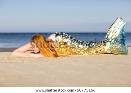 Orange haired mermaid with tail on the beach - stock photo