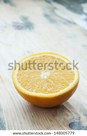 Orange. Half-cut fresh juicy orange on rustic wooden table. Shot at daylight, shallow depth of field. - stock photo