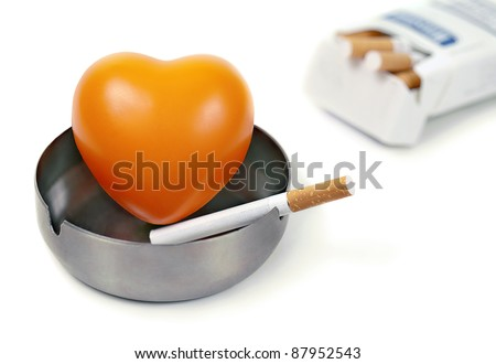"""Orange heart in the ashtray and cigarettes.""""Concept - harm of smoking"""" - stock photo"""