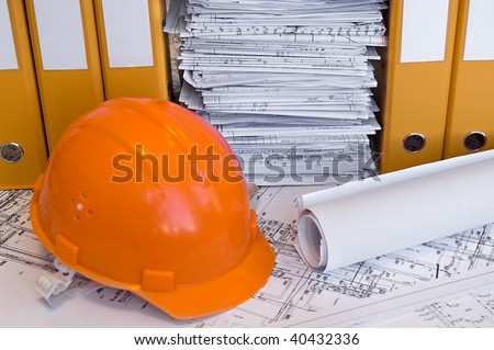 Orange helmet, design drawings and yellow file folders on the table. Business still life - stock photo