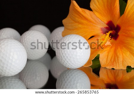Orange hibiscus flower  and golf equipments on the glass plate - stock photo