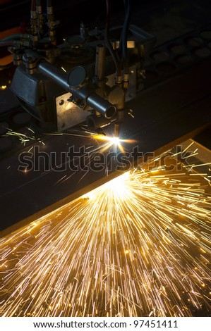 orange hot sparks resulting from industry auto cutter plate machine in low light area - stock photo