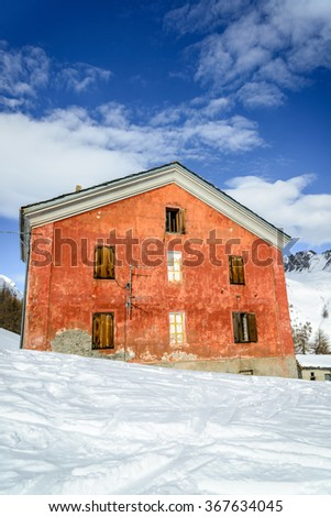 Orange house in the mountains with snow