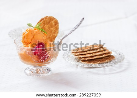 Orange ice cream served in a cup with waffles over white background - stock photo