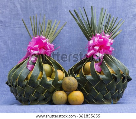 Orange in Coconut leaves two basket on Purple cloth - stock photo
