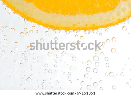 Orange in sparkling water on white background - stock photo