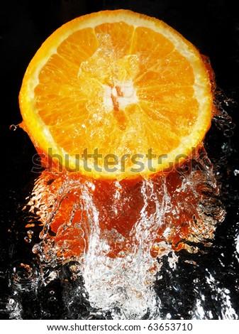 orange in streaming water - stock photo