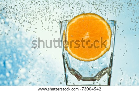 orange in the glass with mineral water - stock photo