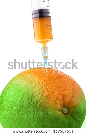 Orange in two colors with a syringe. Concept for genetically modified foods. - stock photo