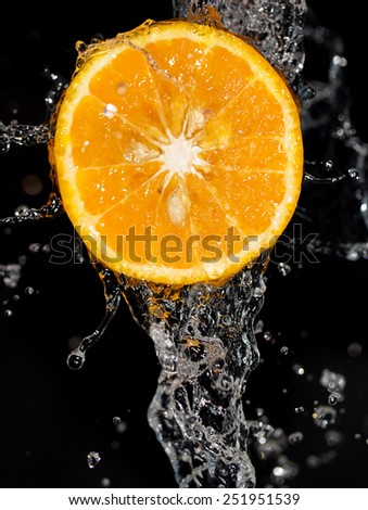 orange in water on a black background - stock photo