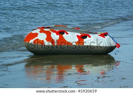 orange inner tube on beach edge ready for action - stock photo