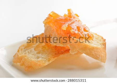 Orange jam and a crisp toast on a white background - stock photo