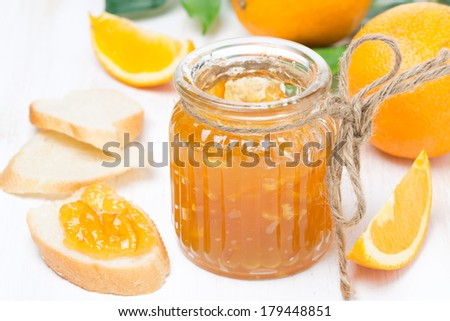 orange jam in a glass jar and fresh bread, close-up - stock photo