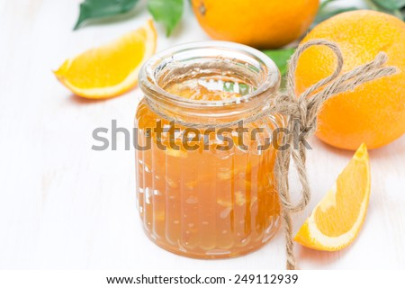 orange jam in a glass jar and oranges on the table, horizontal - stock photo