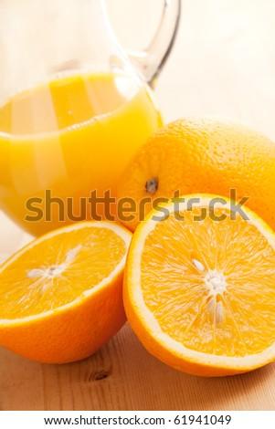 orange juice and orange fruit on wooden table - stock photo