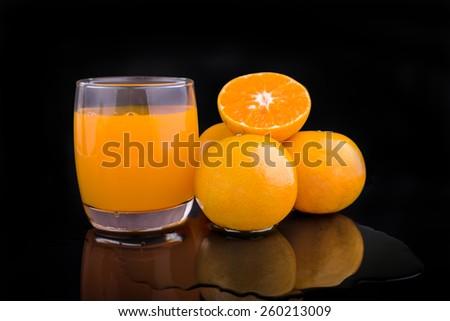 orange juice and slice isolated on black background - stock photo