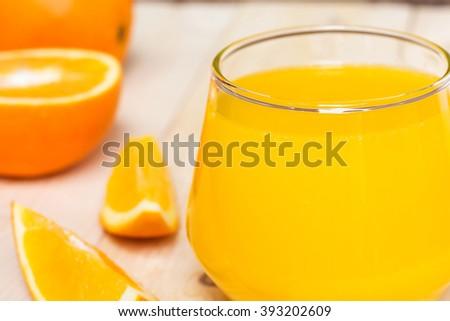 Orange juice and slices of orange on wooden background - stock photo