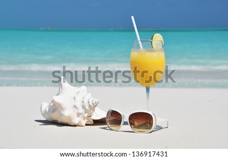 Orange juice and sunglasses on the beach. Exuma, Bahamas - stock photo