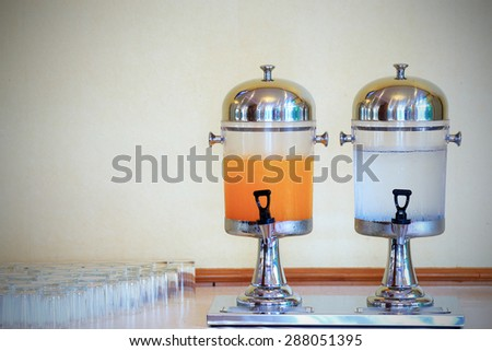 Orange juice and water in dispenser and glasses on table for party - stock photo
