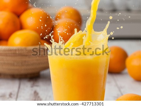 Orange juice being poured in a glass with splash. - stock photo
