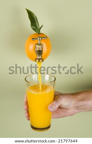 Orange juice being poured into a glass from an actual orange - stock photo